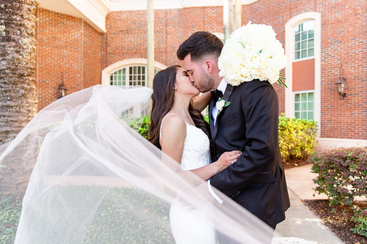 Groom kisses bride as she holds her cream colored bridal bouquet and her white wedding veil blows in the breeze in Davenport, Florida