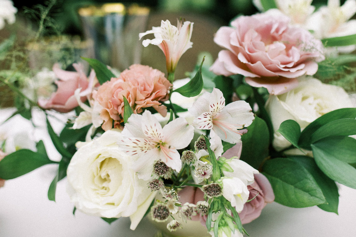Close up of a floral centerpiece with unstructured blooms in mauve, blush and cream