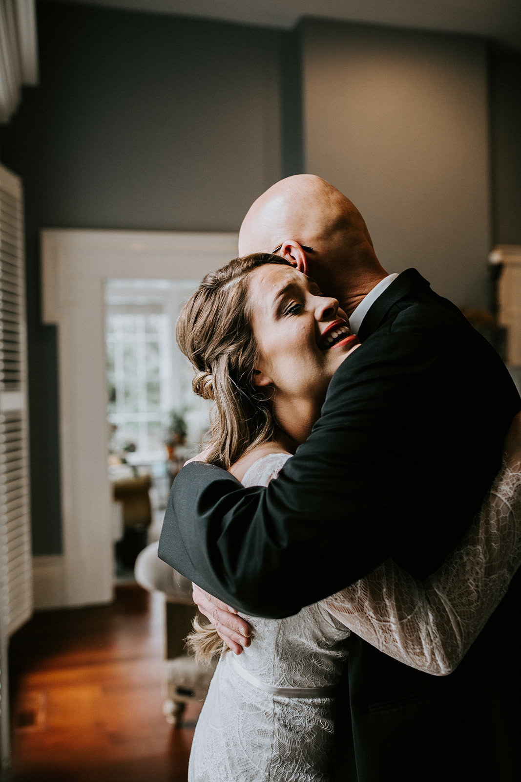 A bride hugs a bald man.
