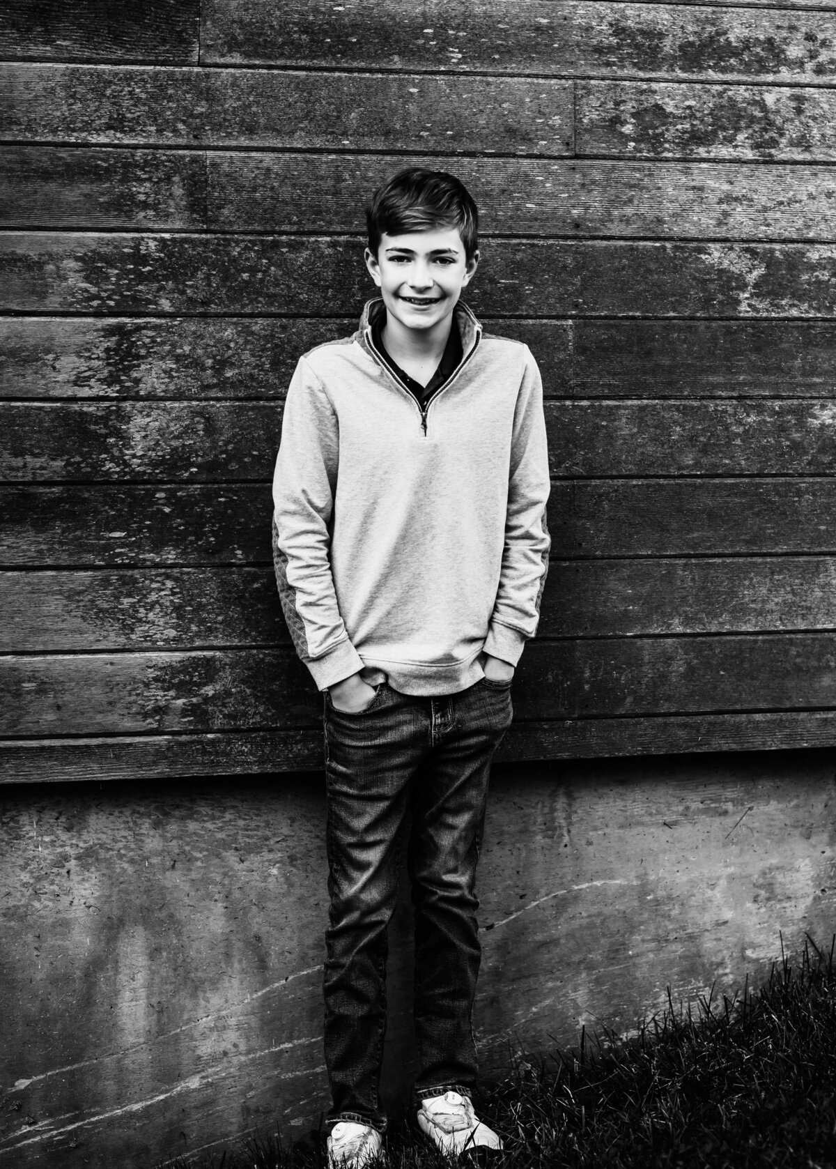 Black and white photo of boy against wall