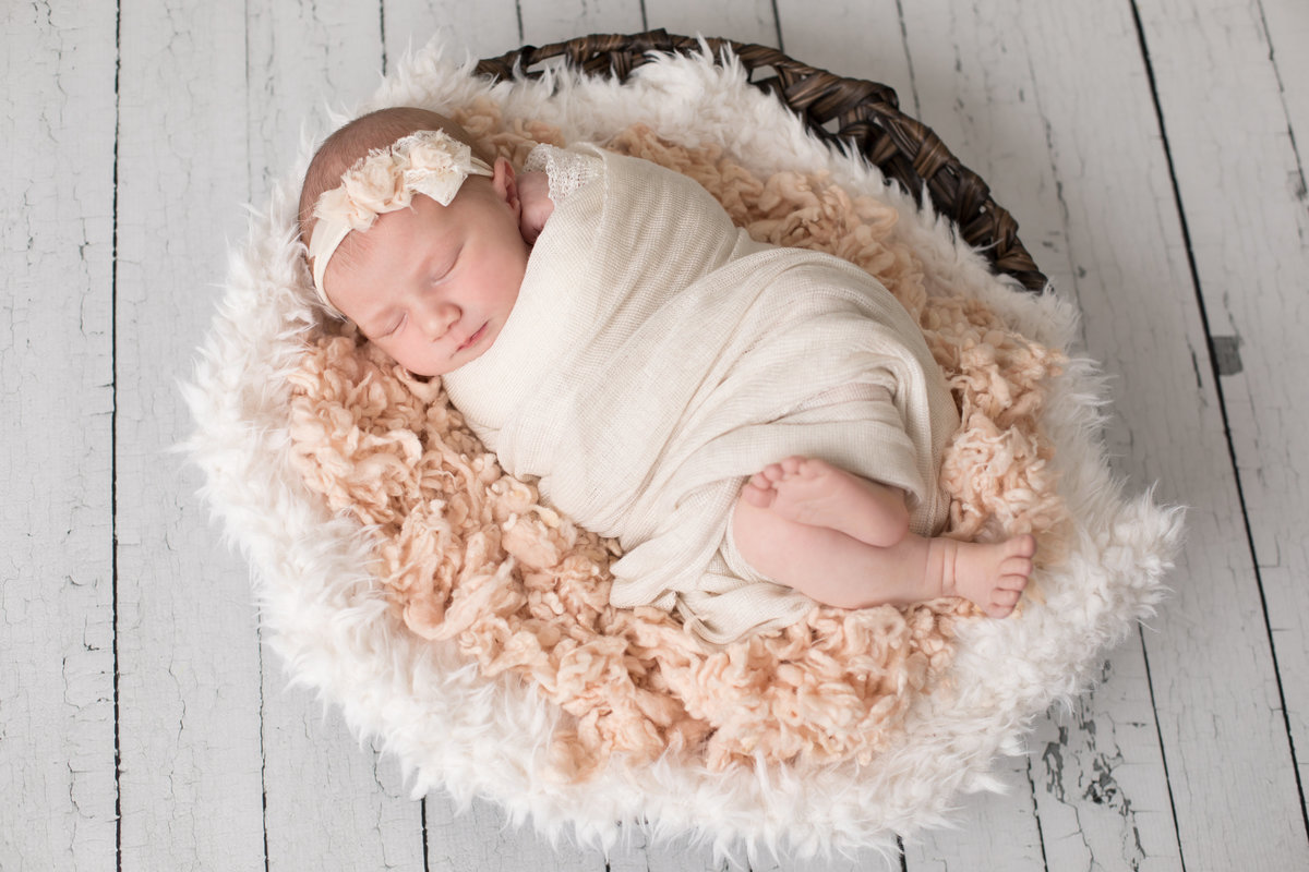 Baby girl in peach wrap sleeping in a fuzzy peach background in a basket