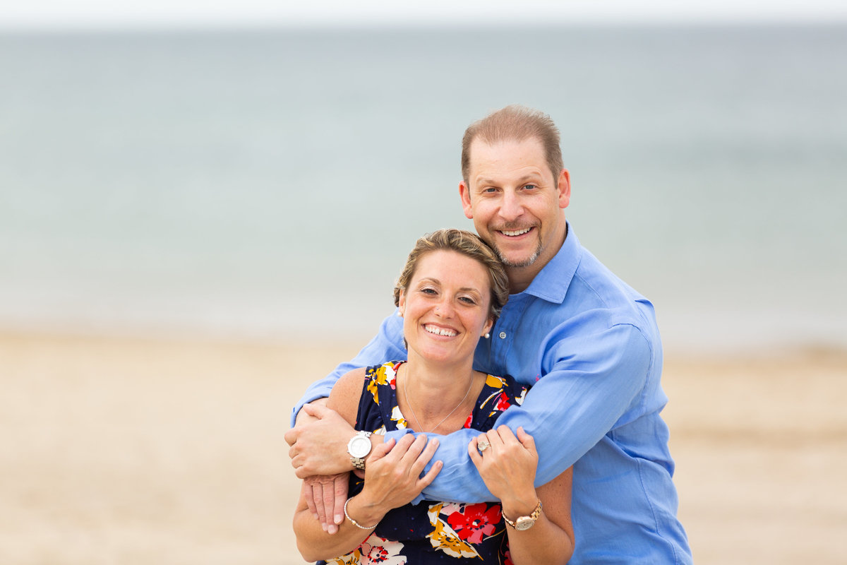 joyful couple on the beach for the engagement photos