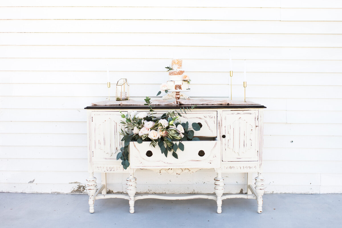A rustic vintage table scape with florals and a wedding cake