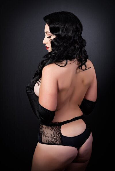 Black haired woman wearing black panties on a black background wearing red lipstick. She is posing for a boudoir photo at Boudoir & Pinup by Janet Lynns studio