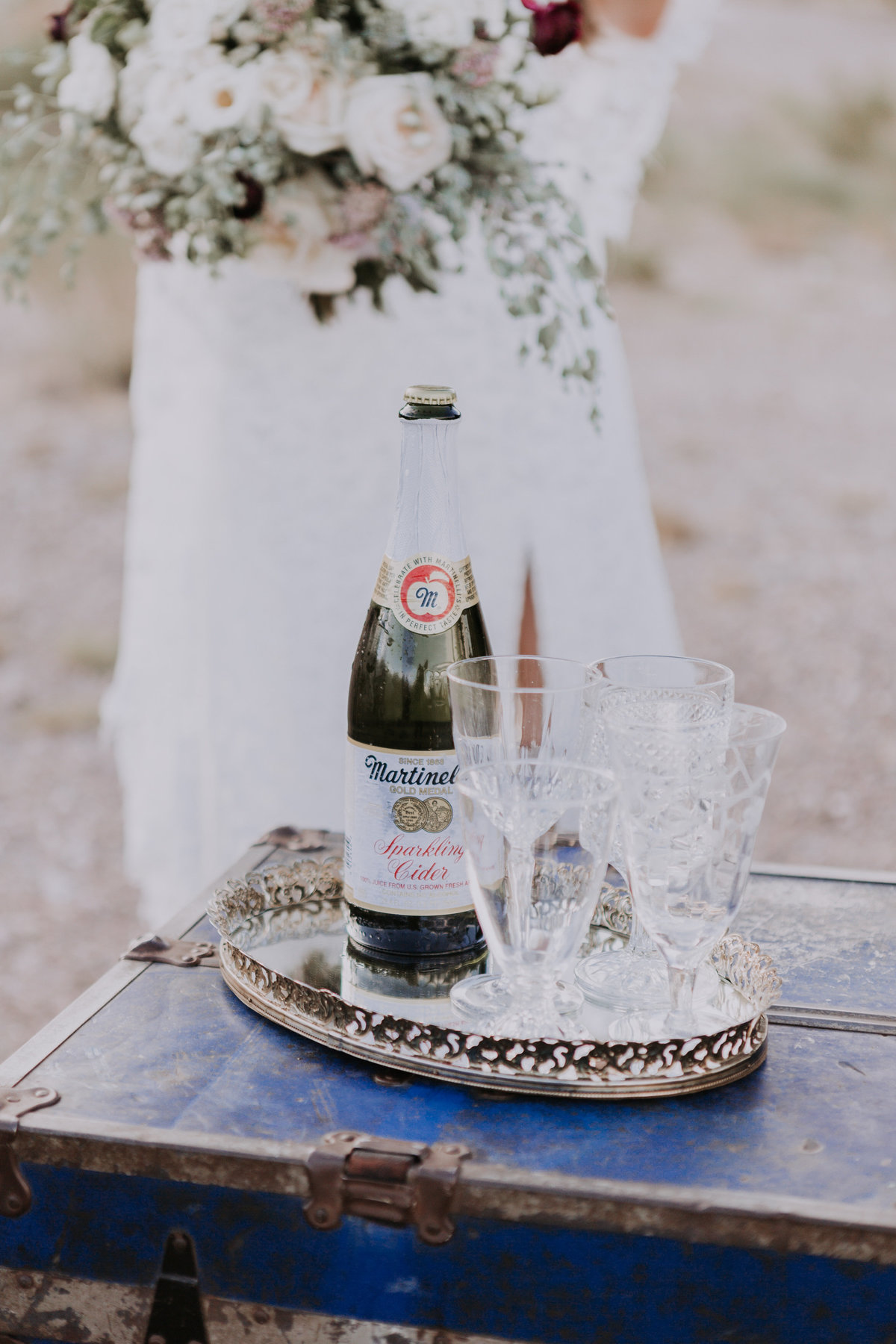 Lake Tahoe elopement photos bride stands behind tray of champagne and glasses