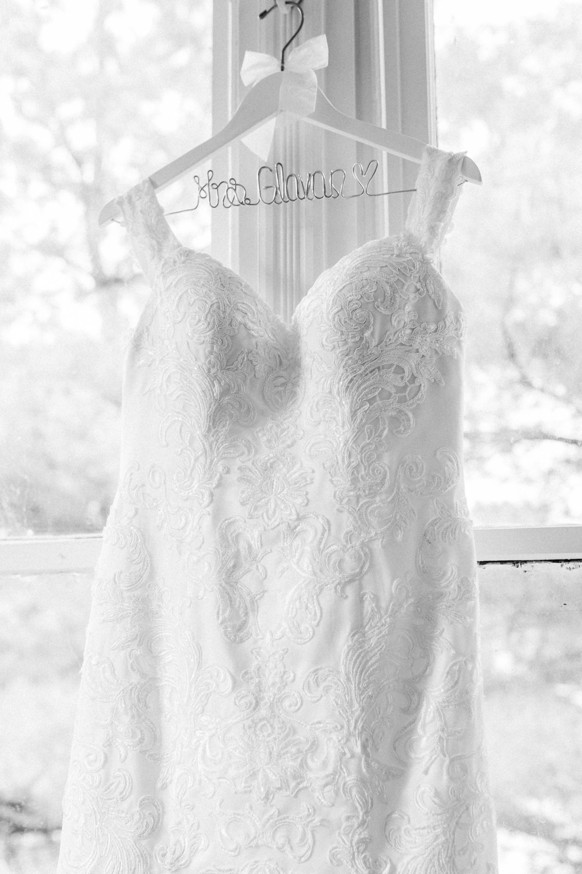 Black and white photo of a wedding dress hanging in a window