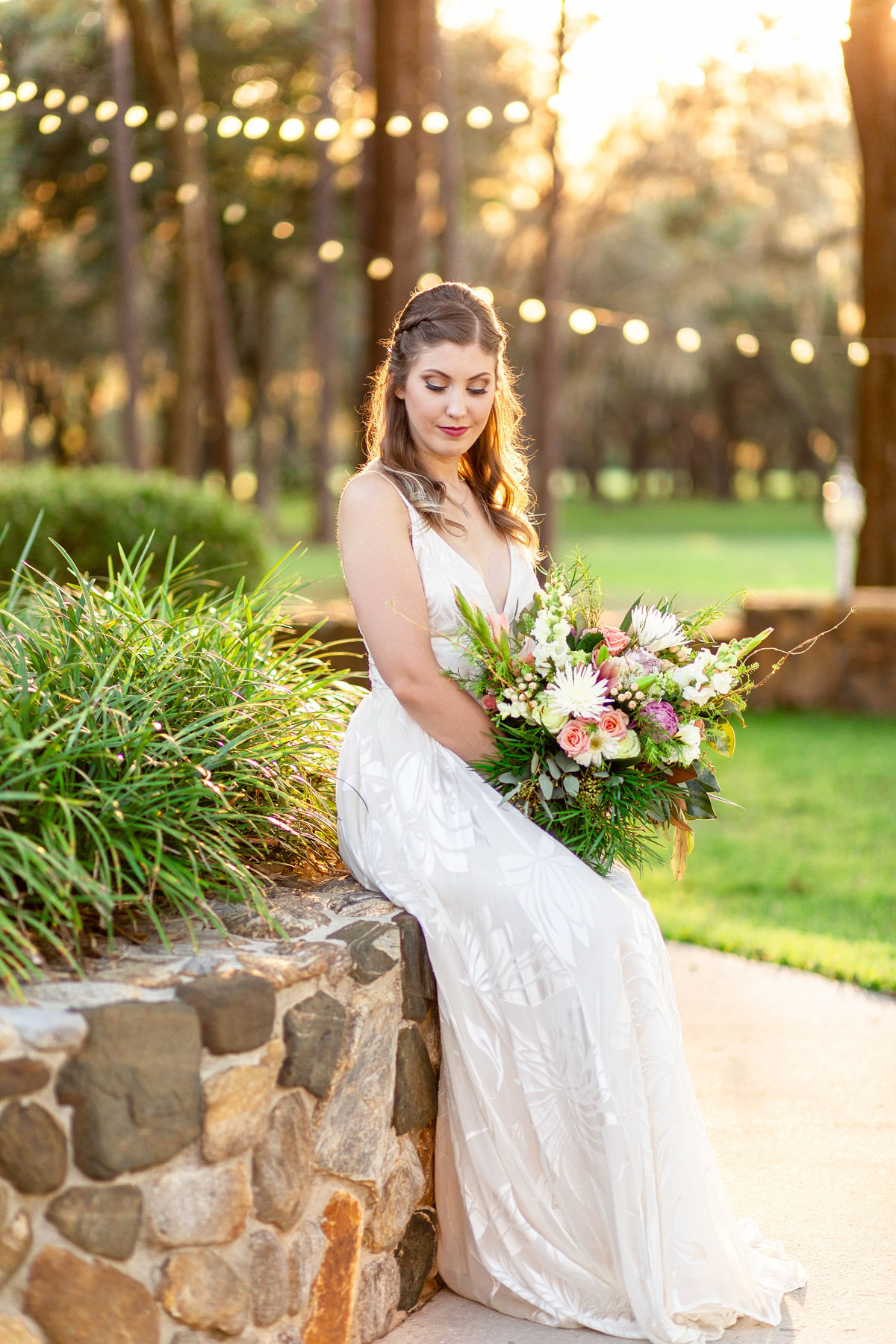 Bride in white wedding dress sits on stone wall at charming wedding venue at sunset with a golden hour glow as she holds her green bridal bouquet with white and pink flowers