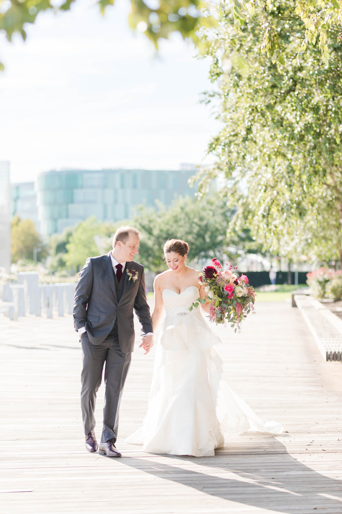 bride and groom walking at navy yard at district winery wedding by costola photography