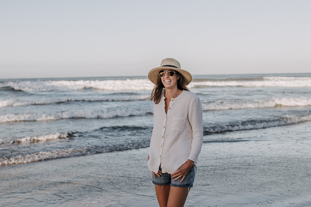 smiling casual woman in hat on beach