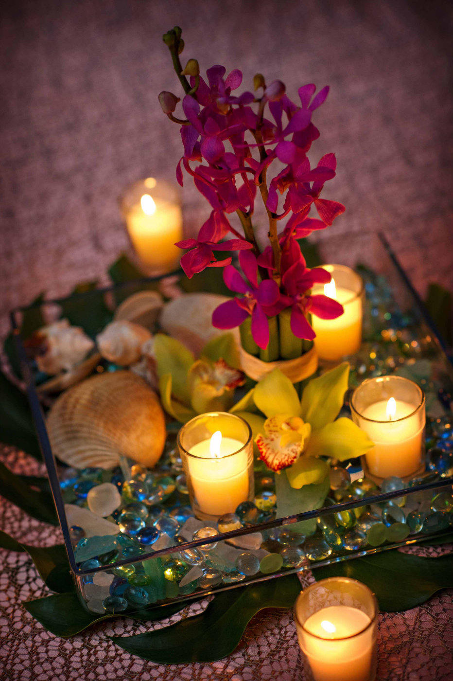 large square centerpiece of red orchid, votives, in square glas sbowl