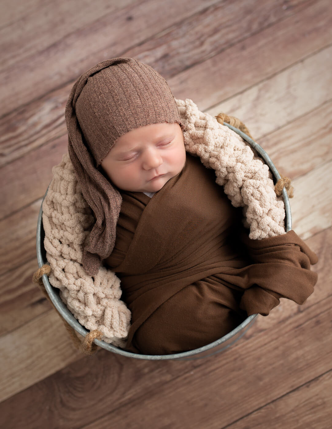 Precious newborn posed in a metal bucket in our studio in Rochester, NY.