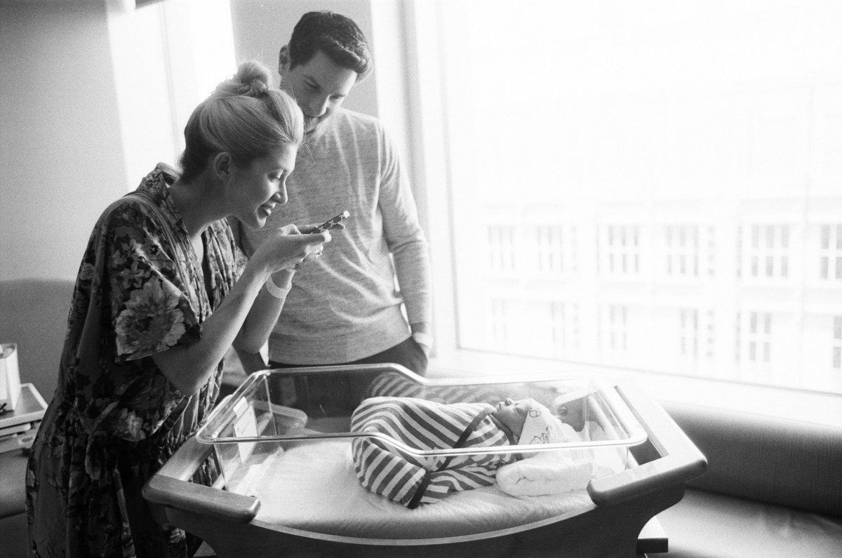 mother taking iphone picture of newborn baby