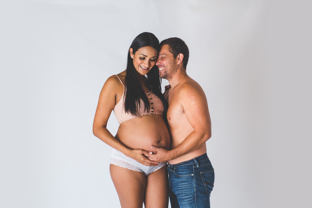 San Antonio Maternity photography in studio session of pregnant couple with man holding woman's belly.