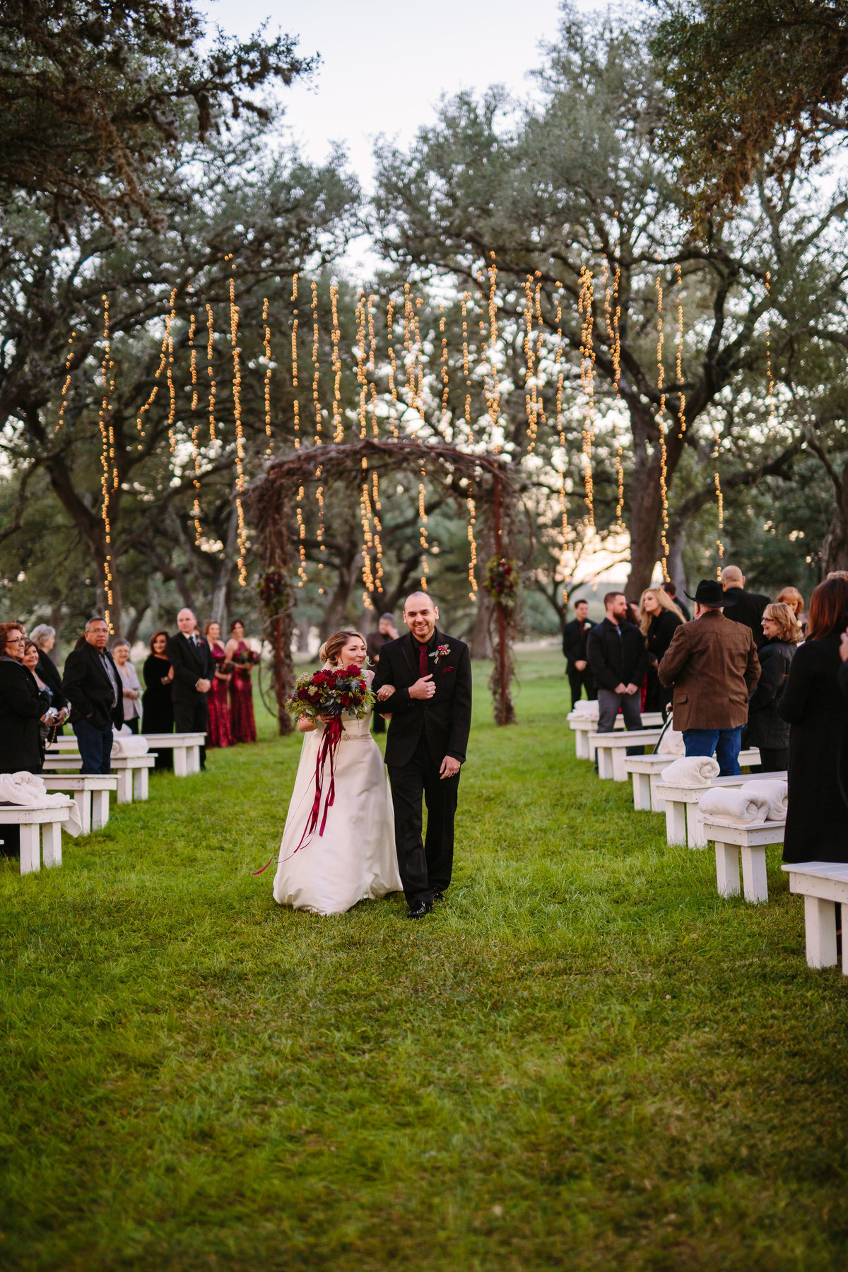 bride and groom exit lit Christmas wedding ceremony site Oaks of Boerne outdoor wedding venue in Texas