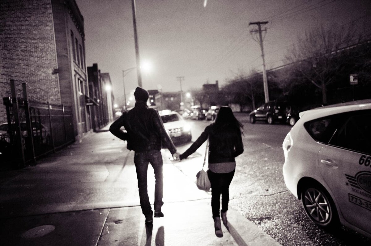 a stylish man and woman walk away holding hands at night lit up by the streelights