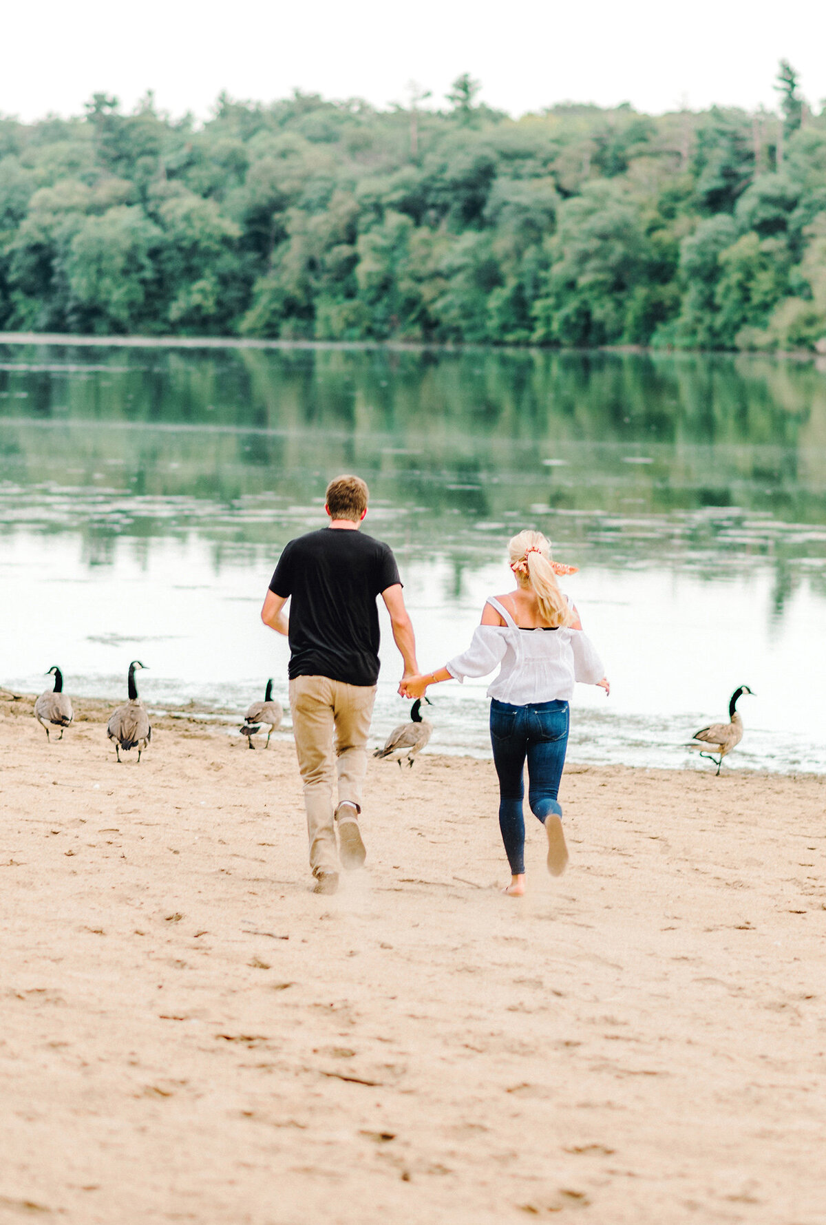 engaged couple runs at pine lake