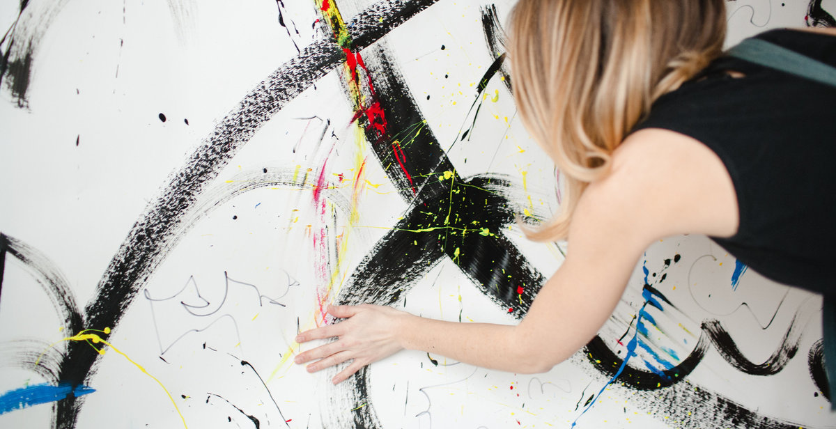 artist painting with her hand on a white background