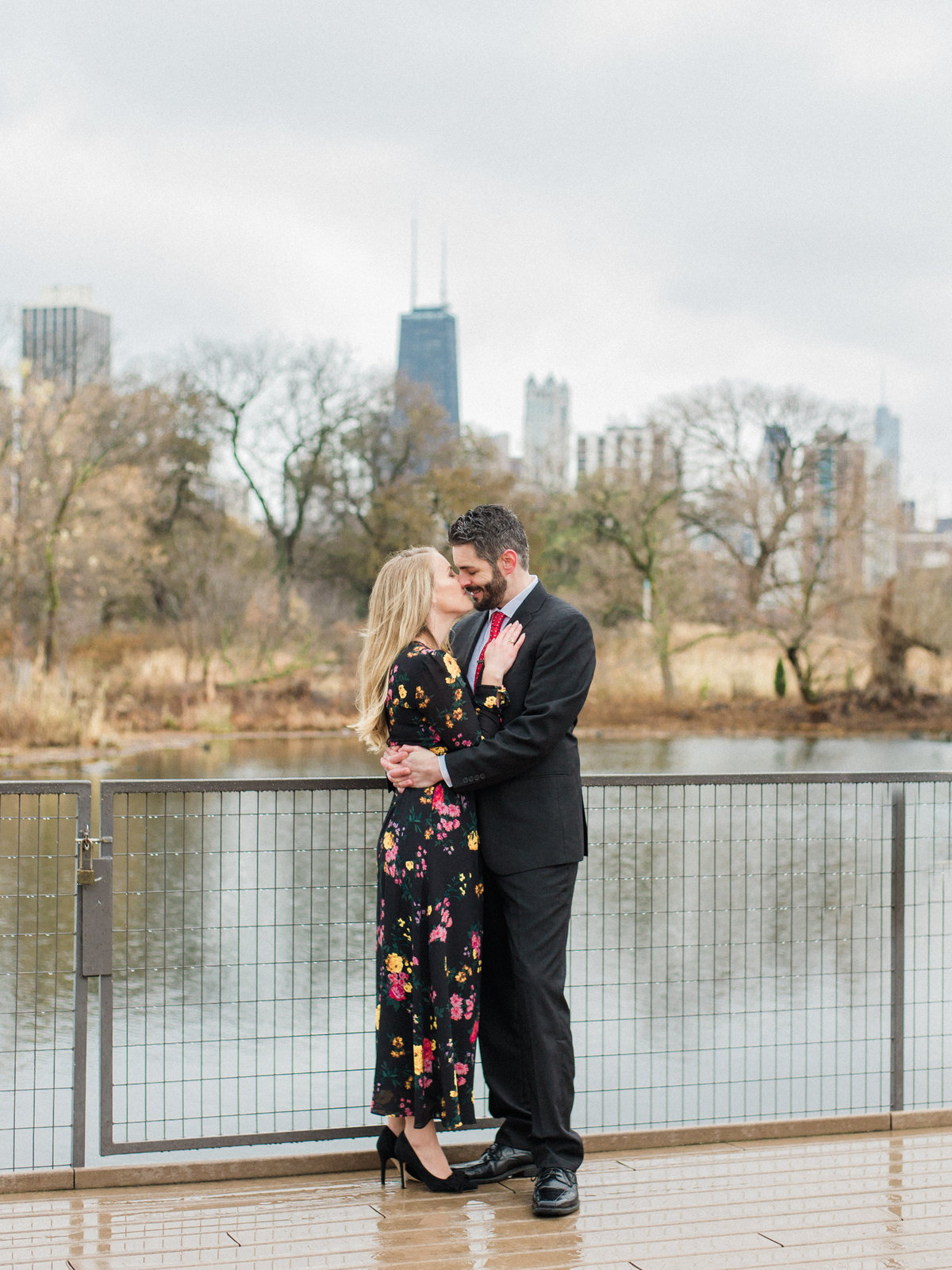 couple hugging on bridge wearing black gown and suit