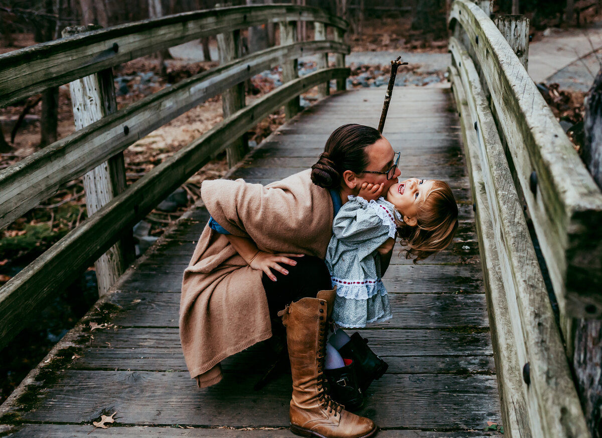 Mom and little girl snuggling on wooden bridge