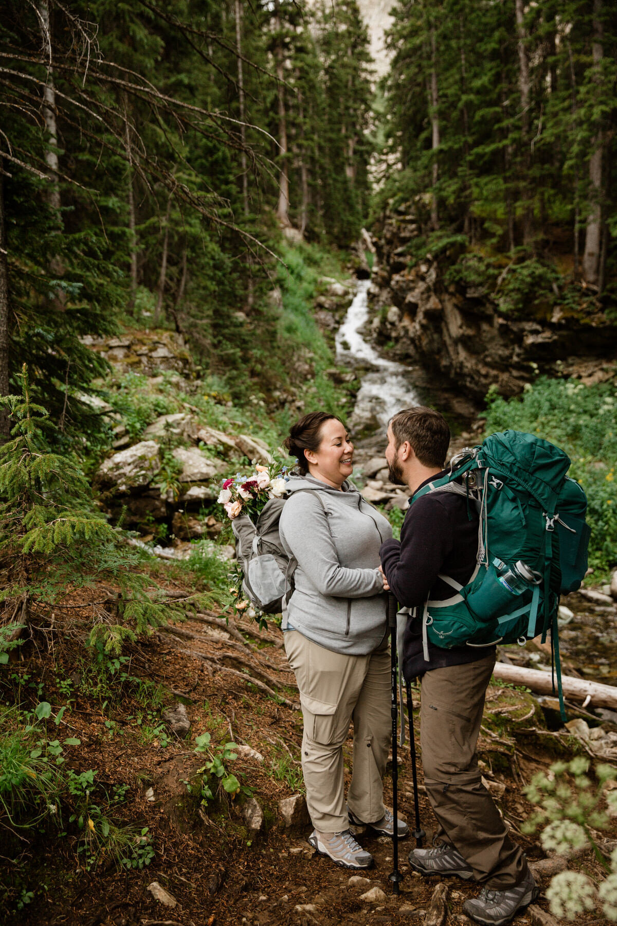 A couple holds each other's hands and smiles at each other while wearing hiking clothes, packs, and with a beautiful forest creek behind them