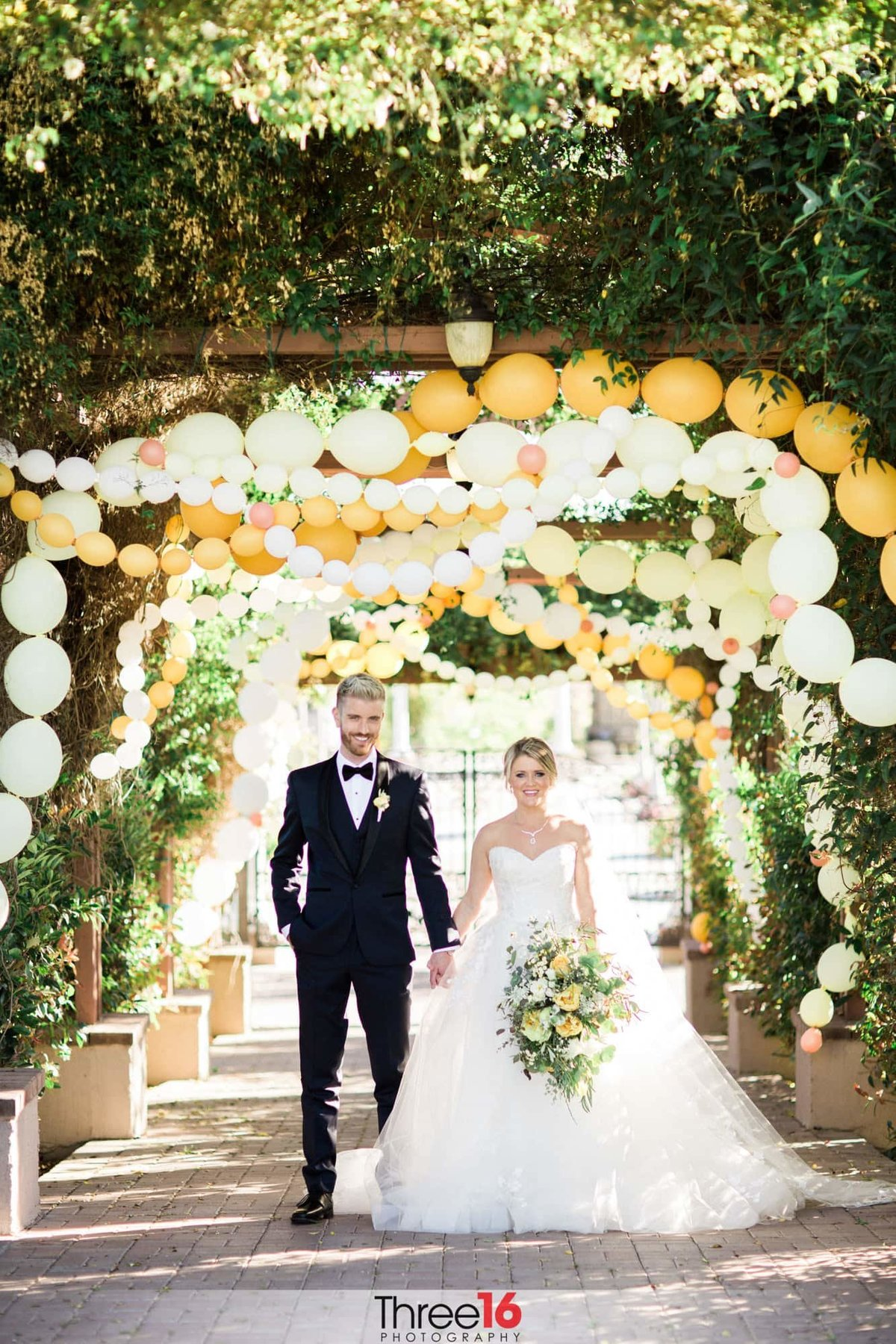 Newly married couple walk under a balloon arch at Mount Palomar Winery Wedding  Venue