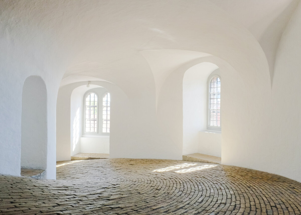 White arches in the ceiling highlight the windows in a brick floor corridor.