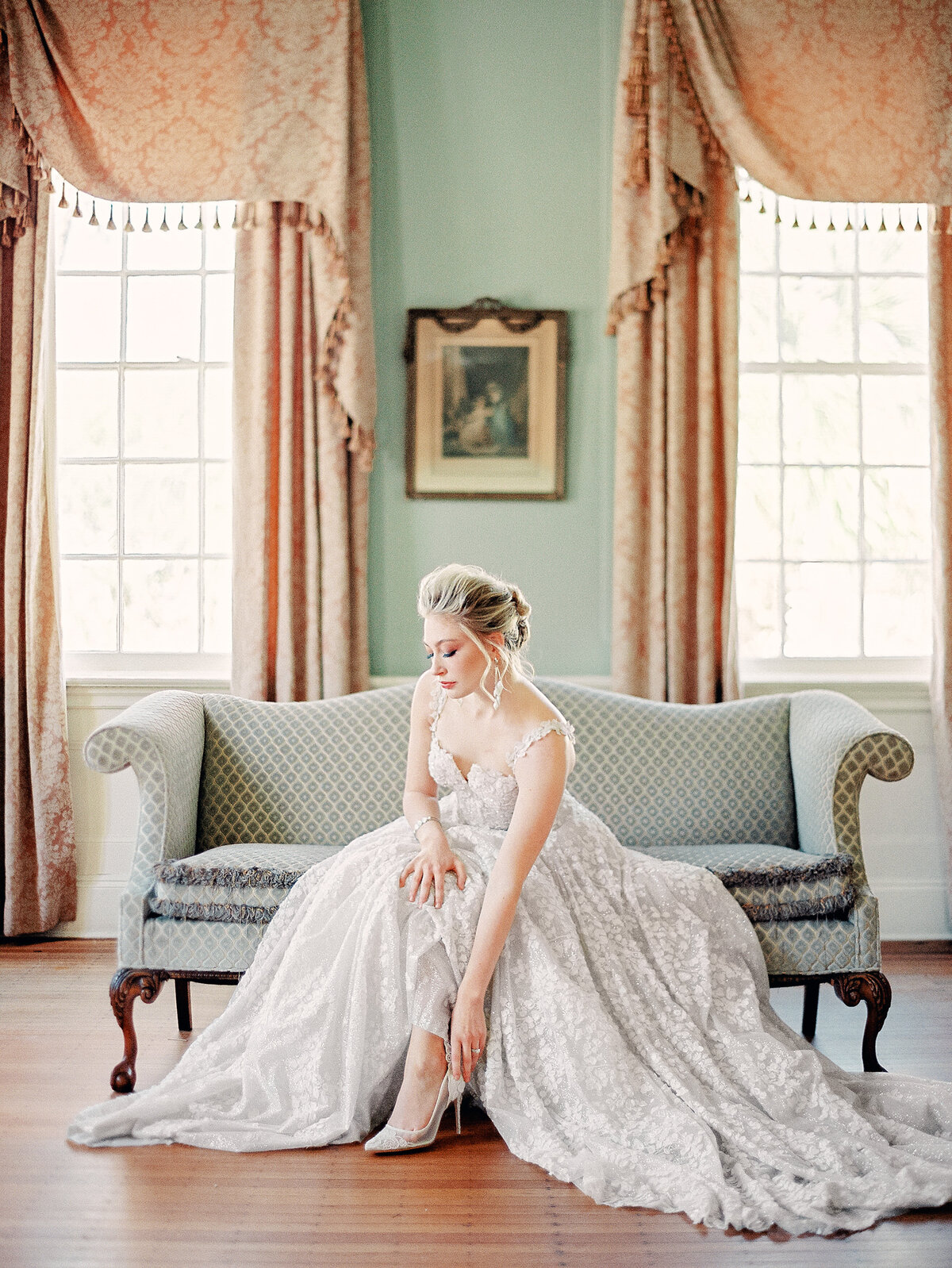 bride in white wedding dress putting on shoes seated on green couch at Lowndes Grove Charleston