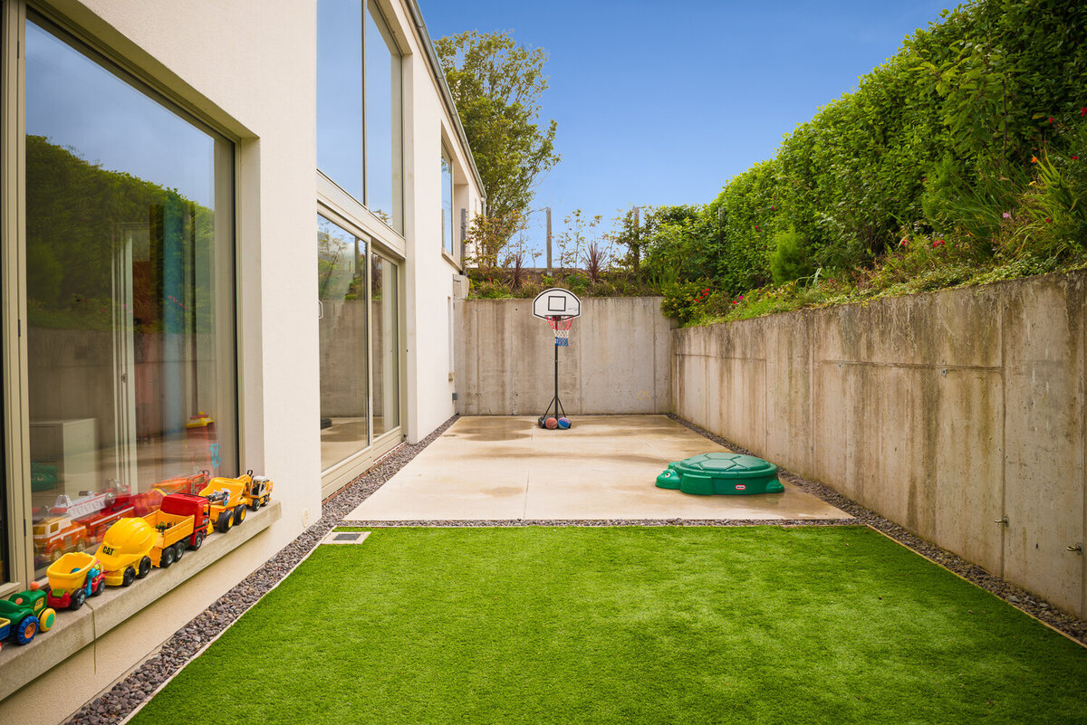 Blow ground level courtyard with faux grass and basketball court