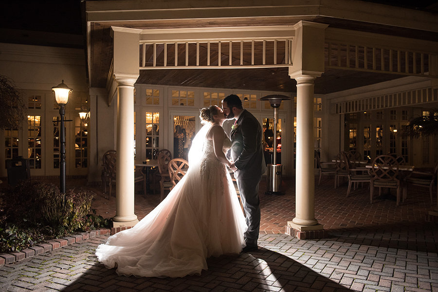 A night photo of a bride and groom on the patio at the Hilton Christiana