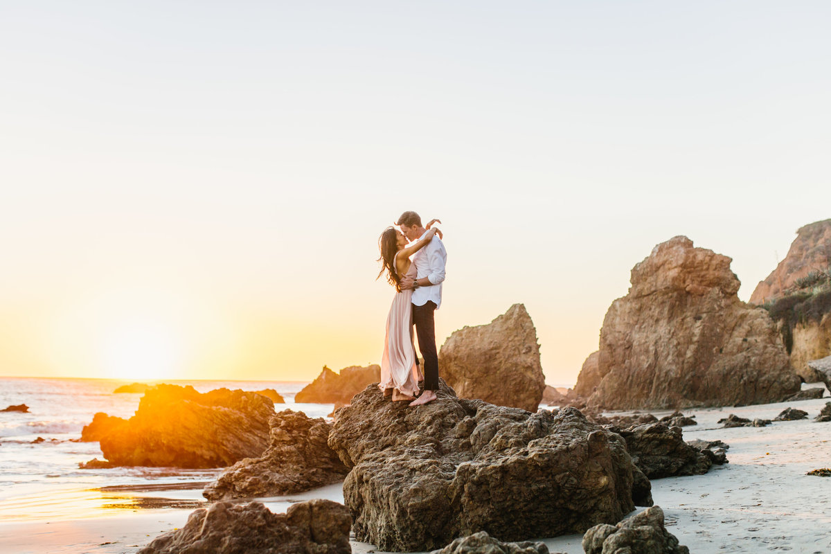 Engagement session photo at the beach on a rock at sunset