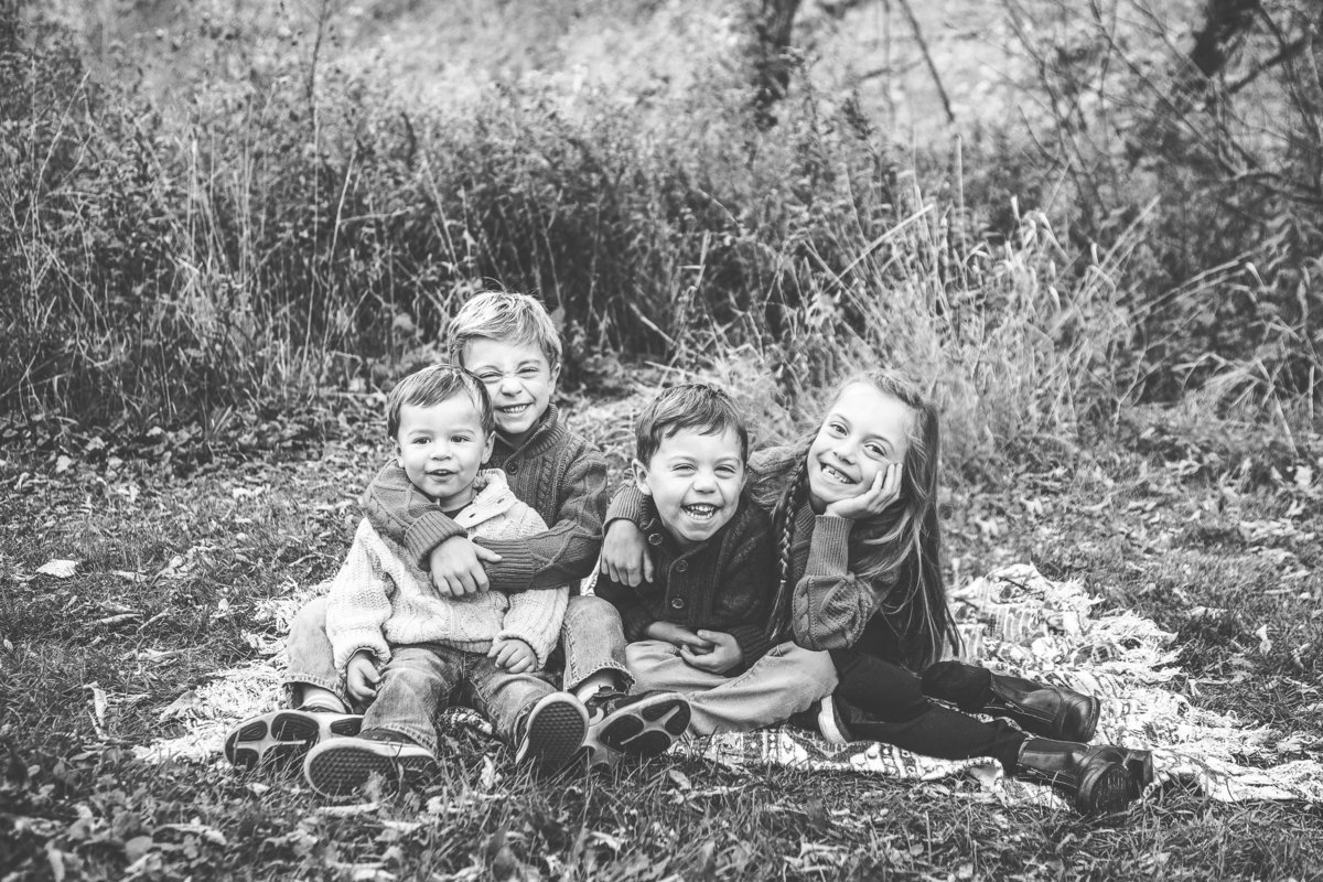 4 young children huddled together laughing outdoors {Burlington Family Photographer}