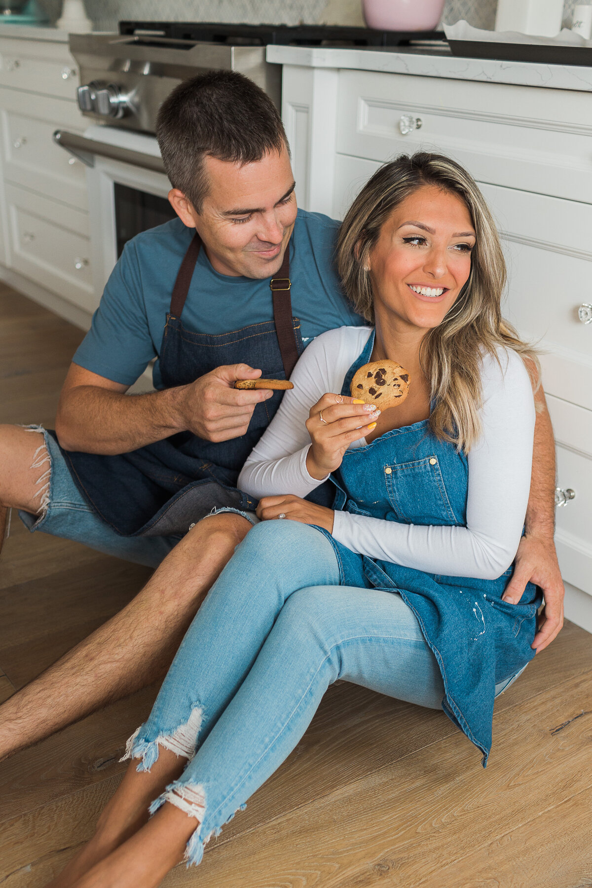 couple sitting on the floor eating chocolate chip cookies