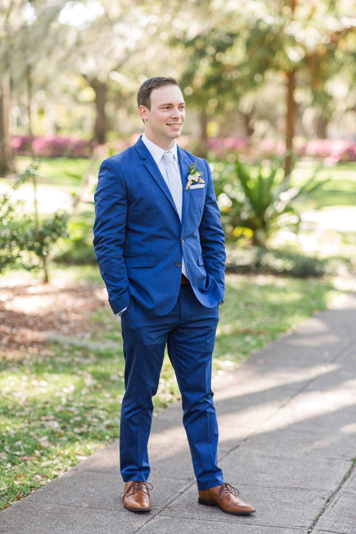 groom satanding alone in blue suit
