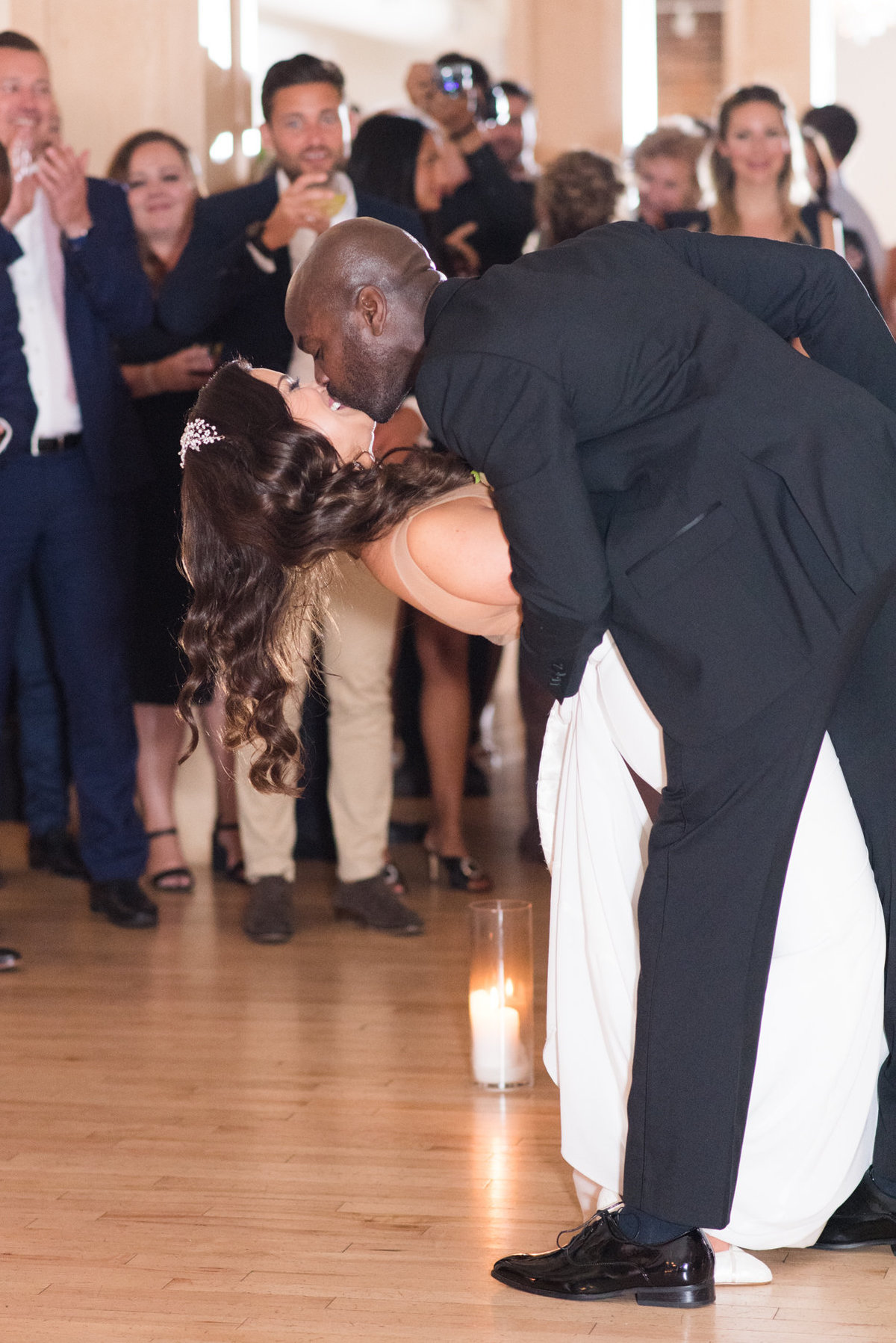 Groom dips his bride for a kiss during their first dance at The Chanterelle in Thunder Bay