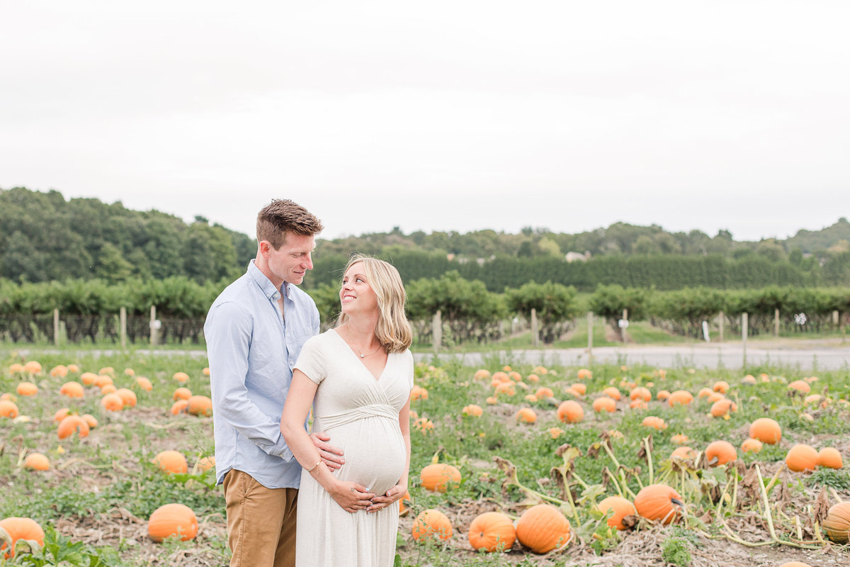 Pregnant woman smiles at husband in pumpkin patch at Lookout Farm Natick MA
