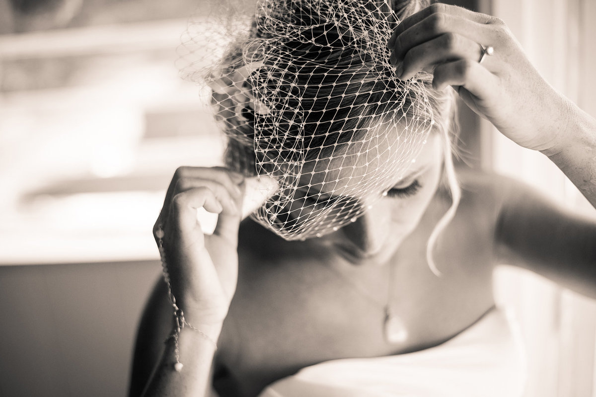 Bride adjusting veil  for her big day in b&w