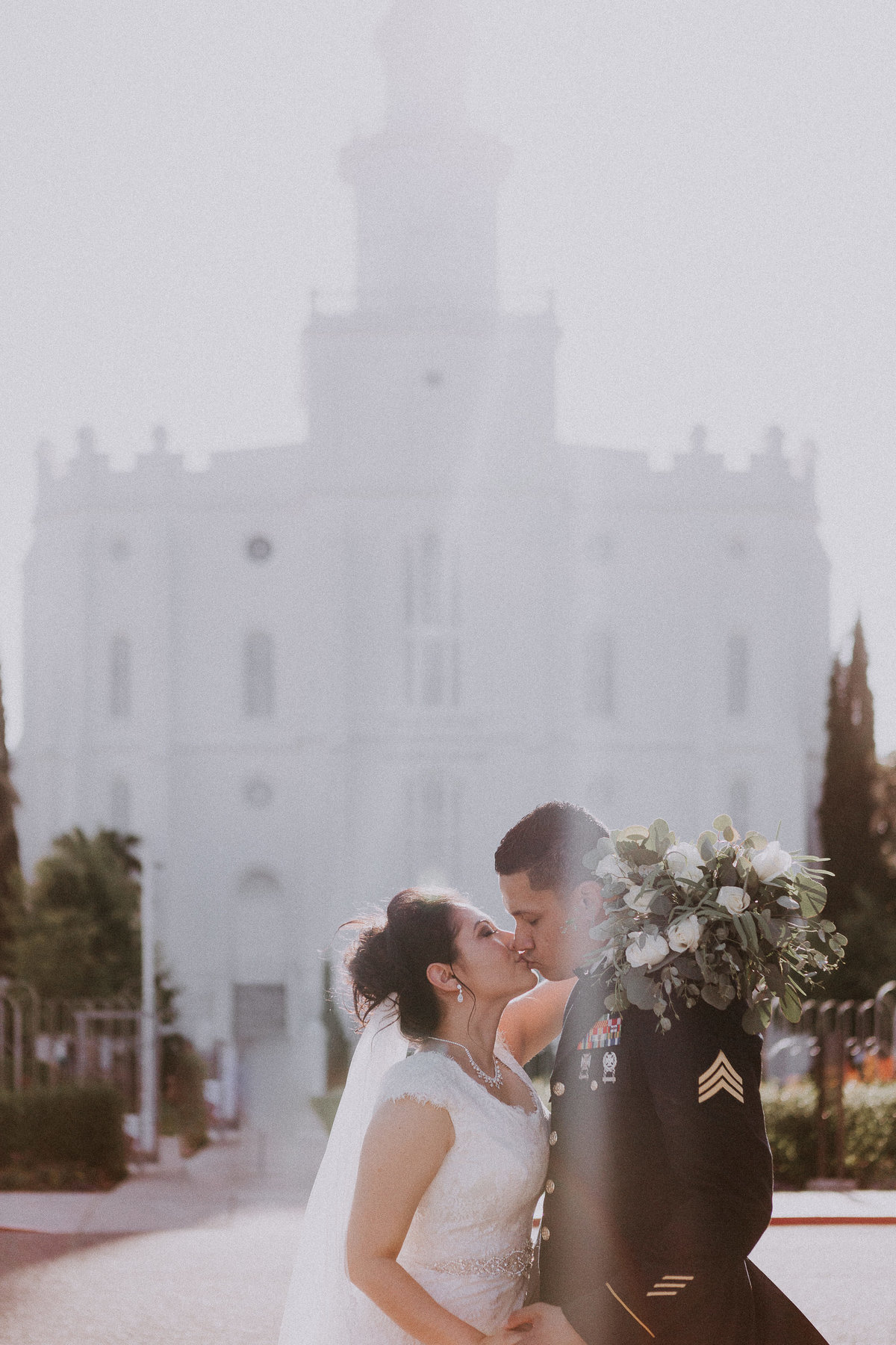 Utah wedding photographers couple kisses in front of temple