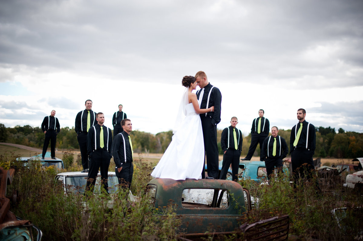bride groom and weddign party standing on top of cars in a junkyard