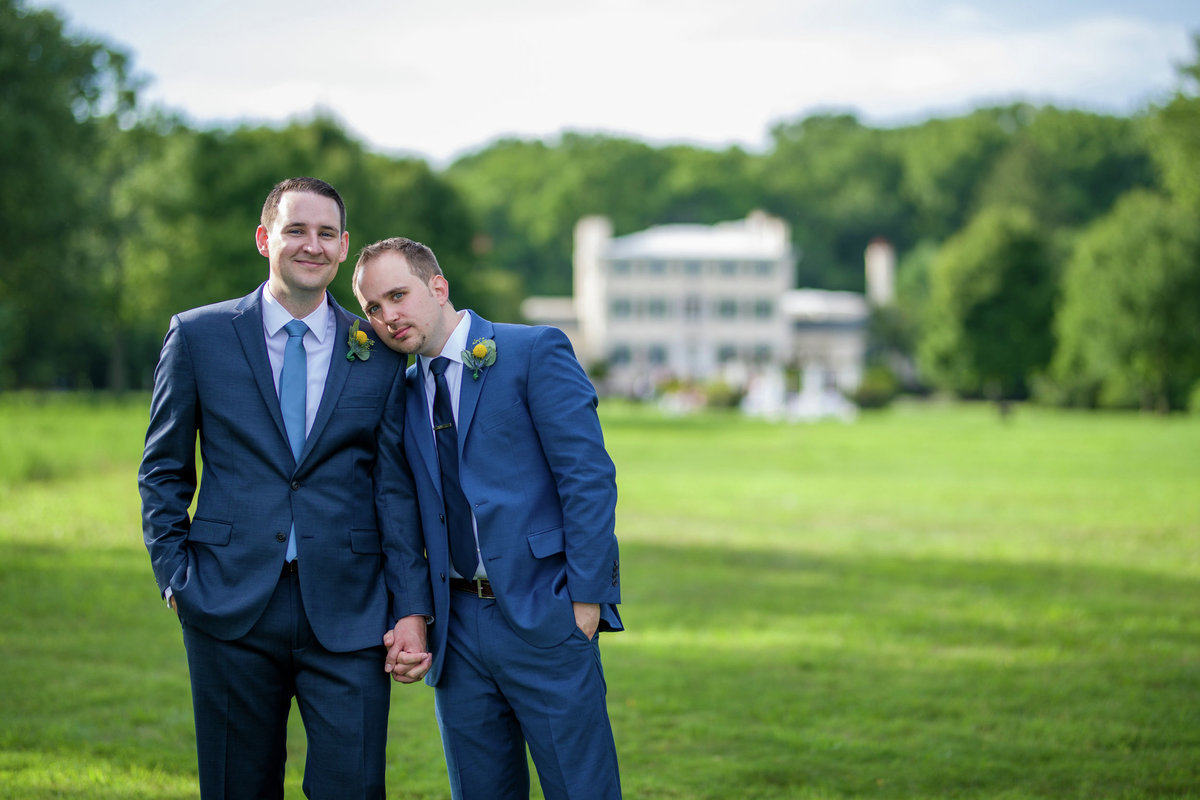 Two grooms holding hands on wedding day
