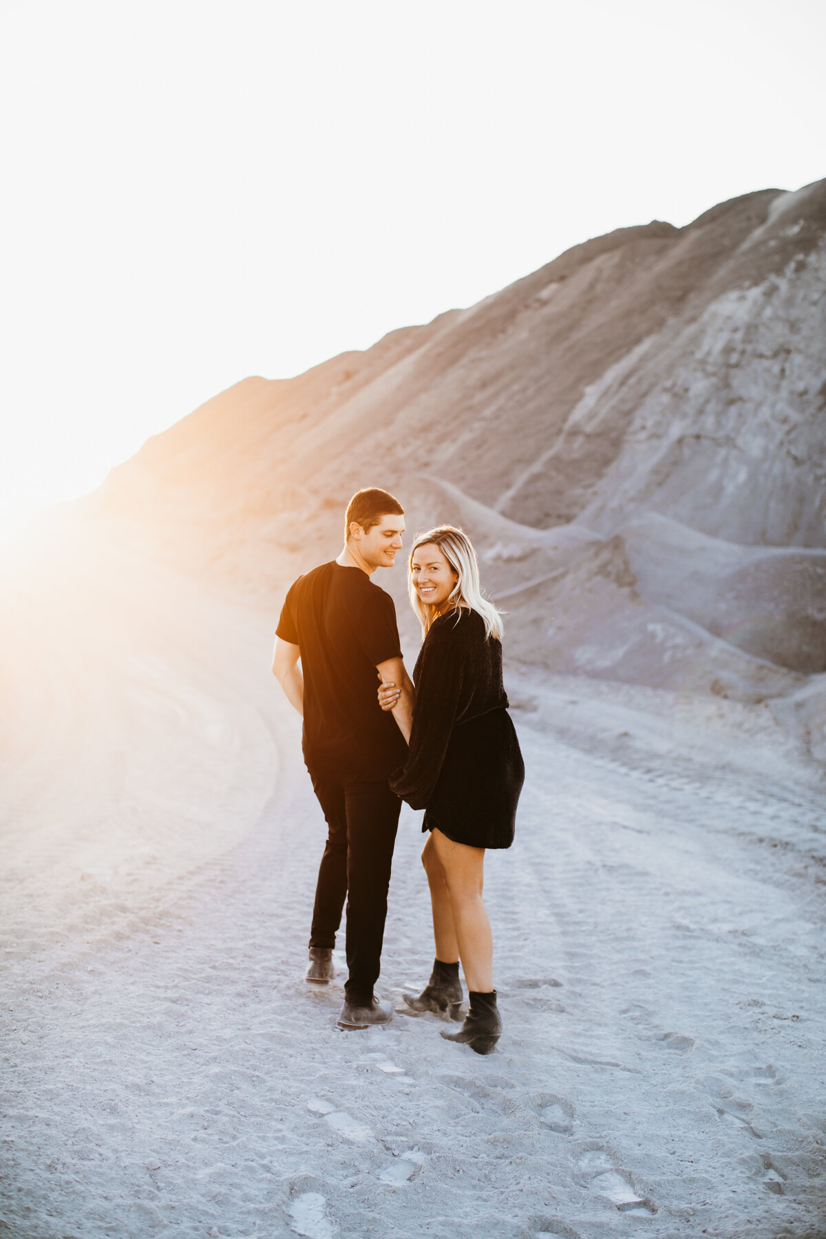 couple walking in the sand at sunset smiling