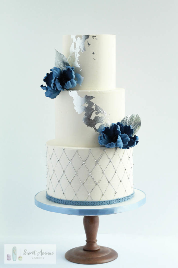 white wedding cake with silver leaf foil and blue flowers