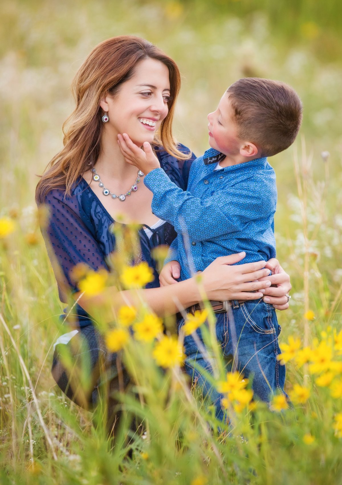 A mother embracing  her small son in a Laramie field with yellow flowers
