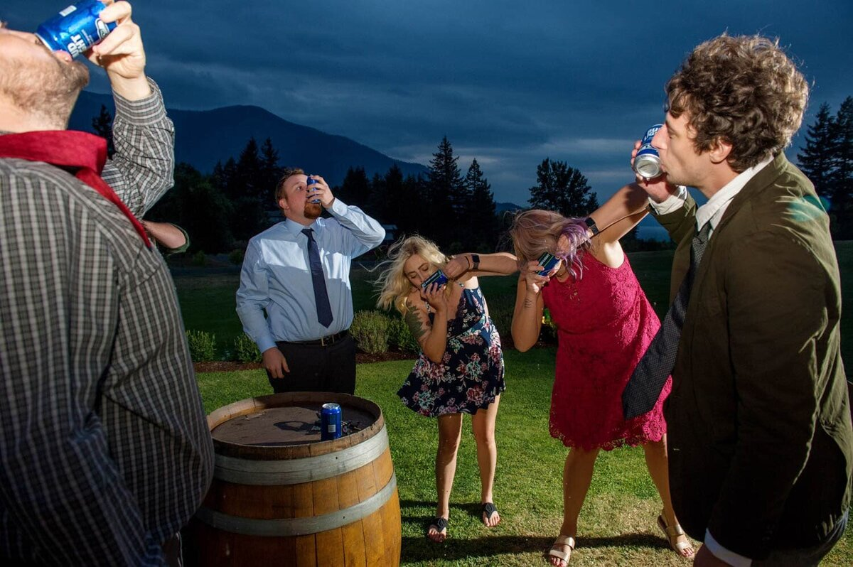 wedding guests shotgun beer during the reception as the sun sets