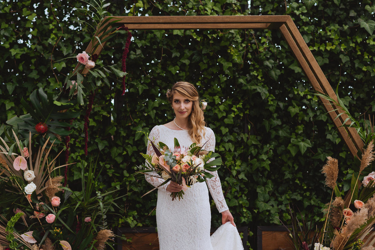 boho bride holding tropical bouquet at greenhouse wedding
