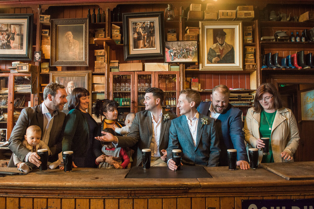 Grooms in traditional Irish pub having fun with guests