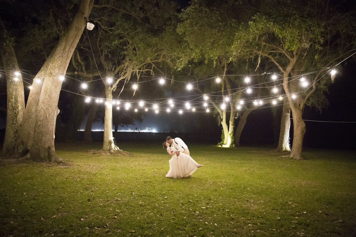 Bride and Groom share a kiss under string lights at the old place in gautier