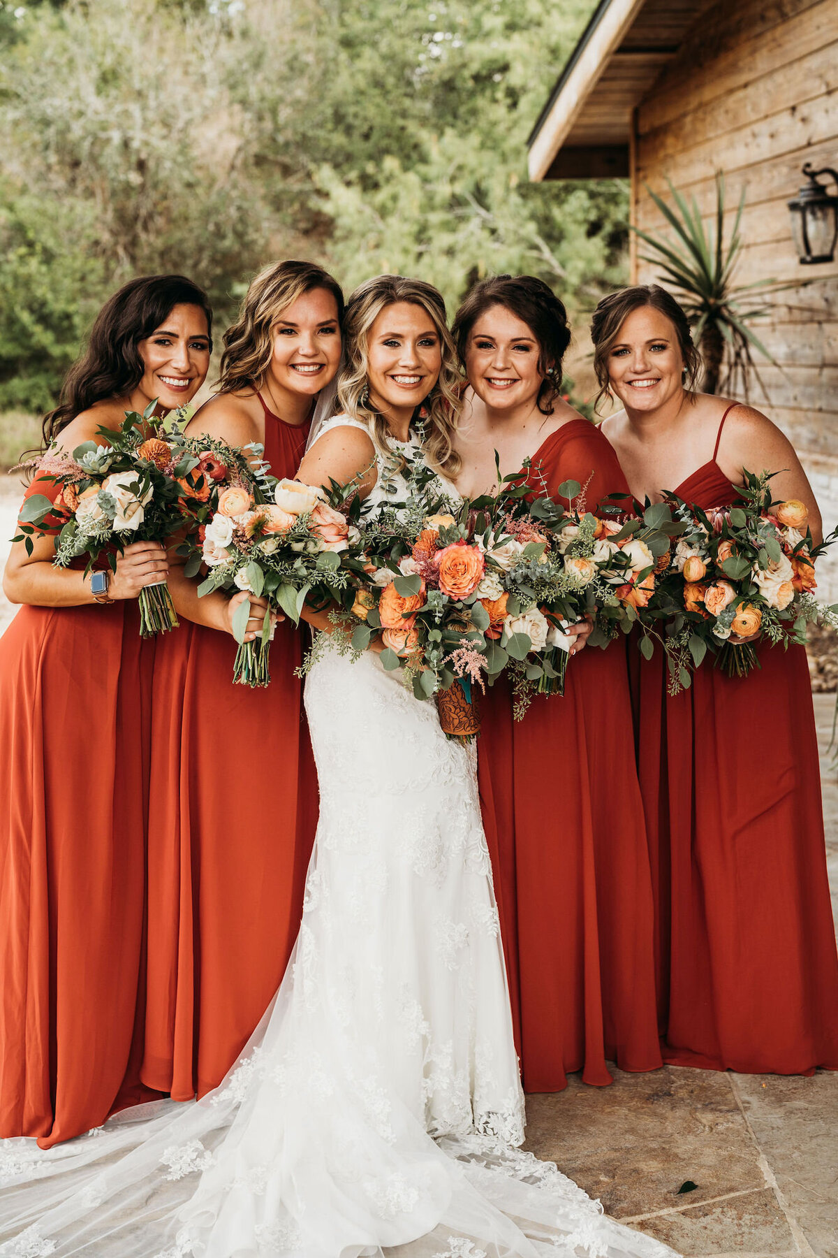 Bride with bridesmaids in red orange dresses and orange florals