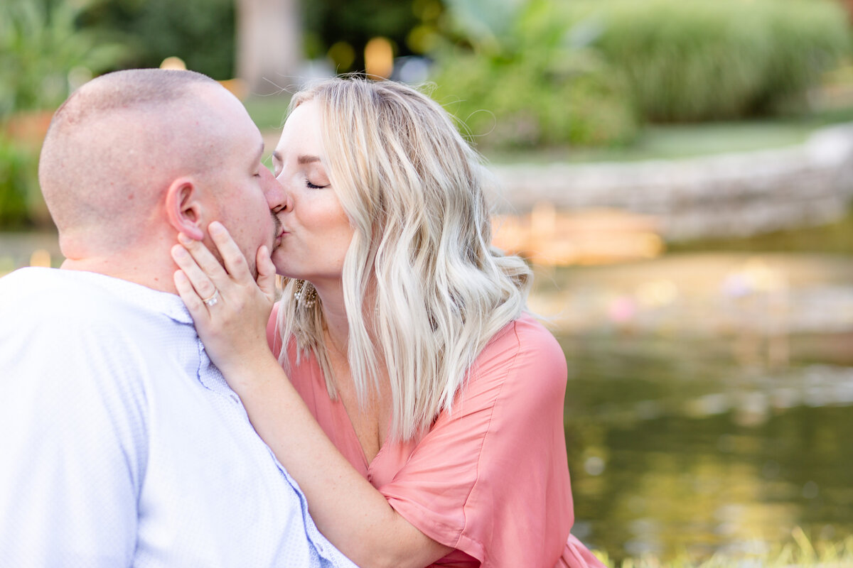 Summer Sunset Engagement Session with pink maxi dress couple kissing  by water  in Tower Grove Park in St. Louis by Amy Britton Photography Photographer in St. Louis