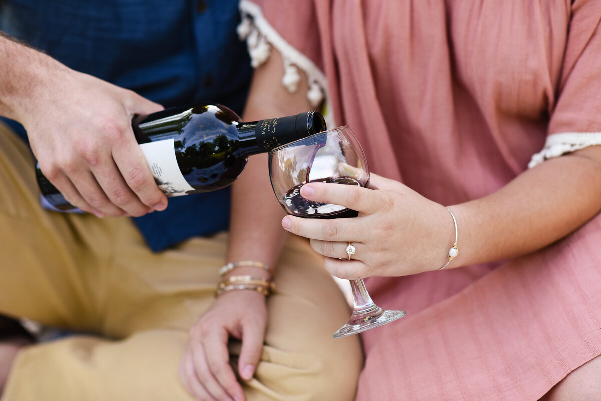 Beautiful Mississippi Engagement Photography: couple enjoys wine at engagement picnic in Mississippi