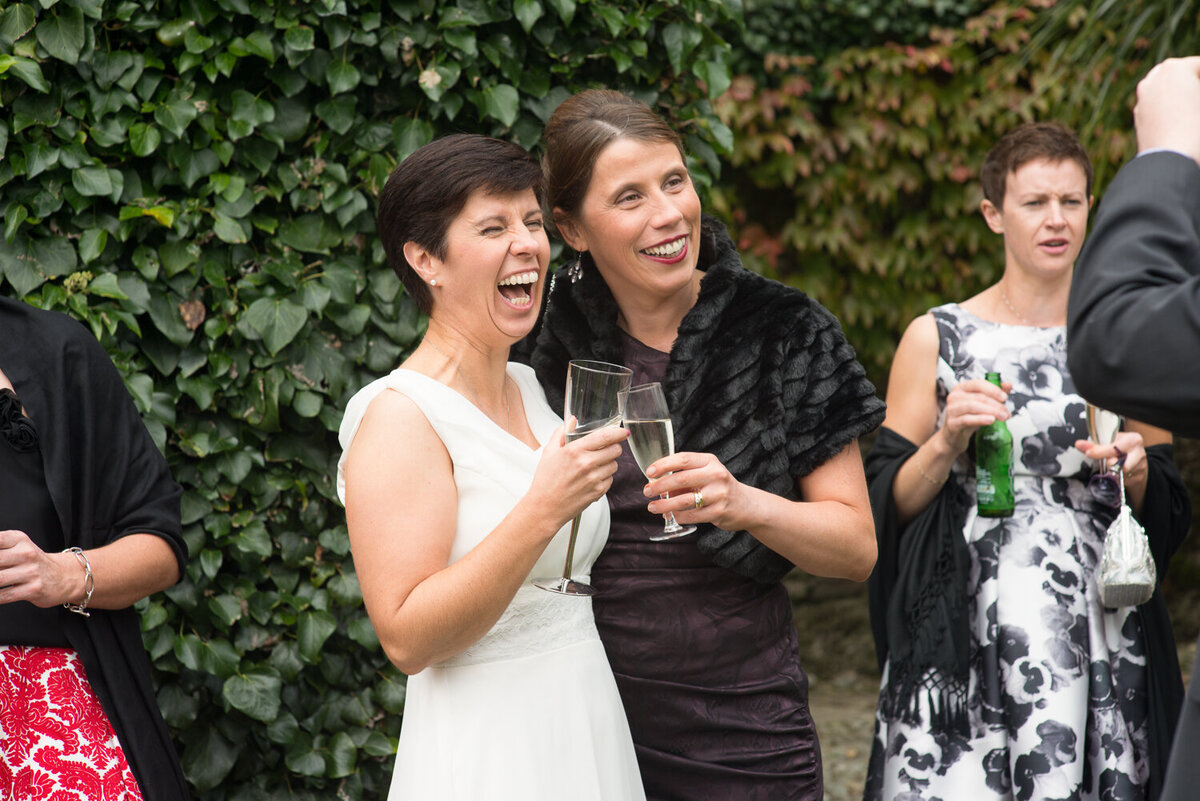 Bride in white laughing with guest in black, holding champagne